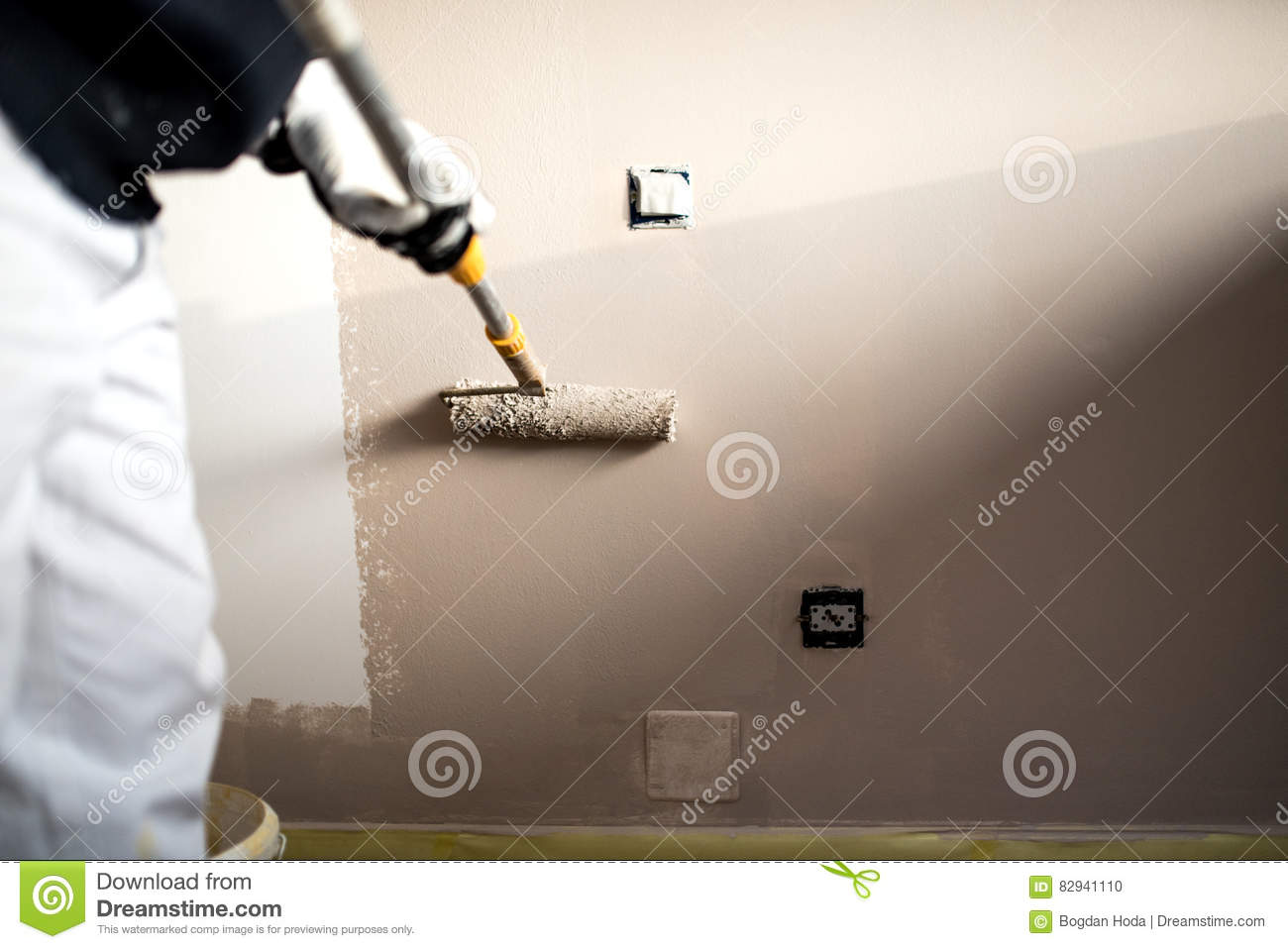 Man decorating walls with paint. Construction plaster worker painting and renovating with professional tools