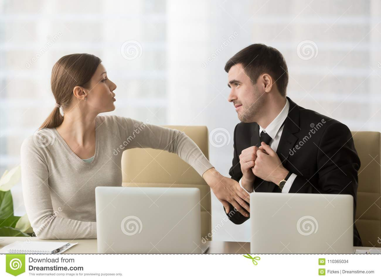 Businessman asking female colleague about favor