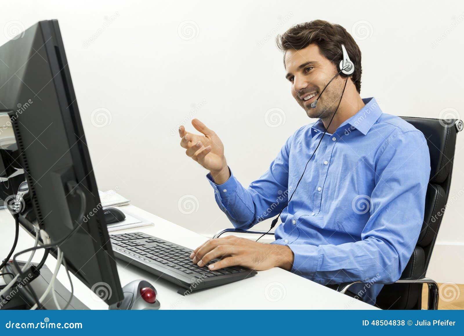 Man den bärande hörlurar med mikrofon som ger online-pratstund och, stötta