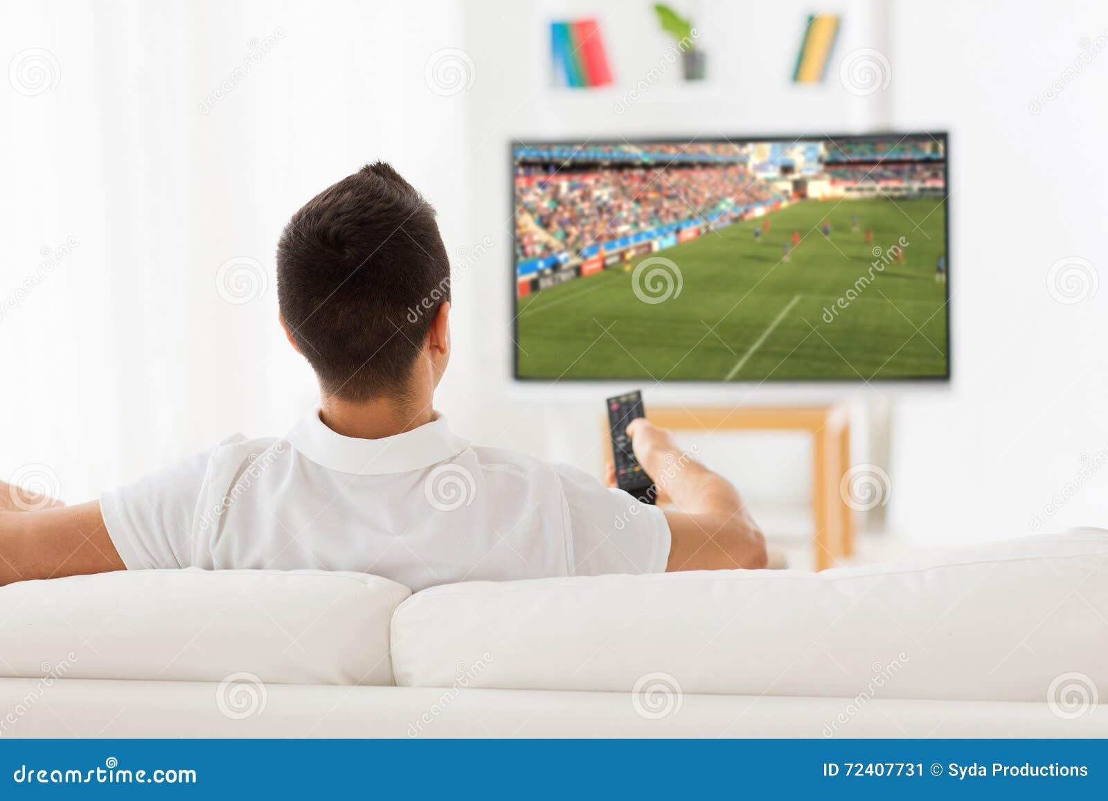 Man den hållande ögonen på fotboll- eller fotbollleken på tv hemma