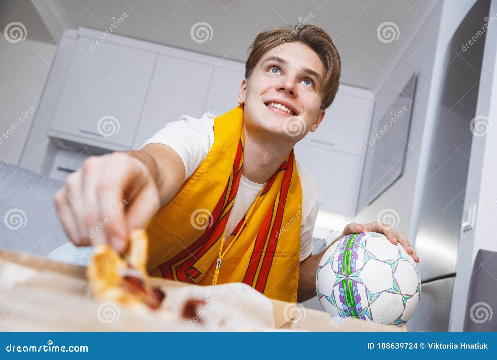 Man den hållande ögonen på sporten på ensam ätapizza för tv hemma