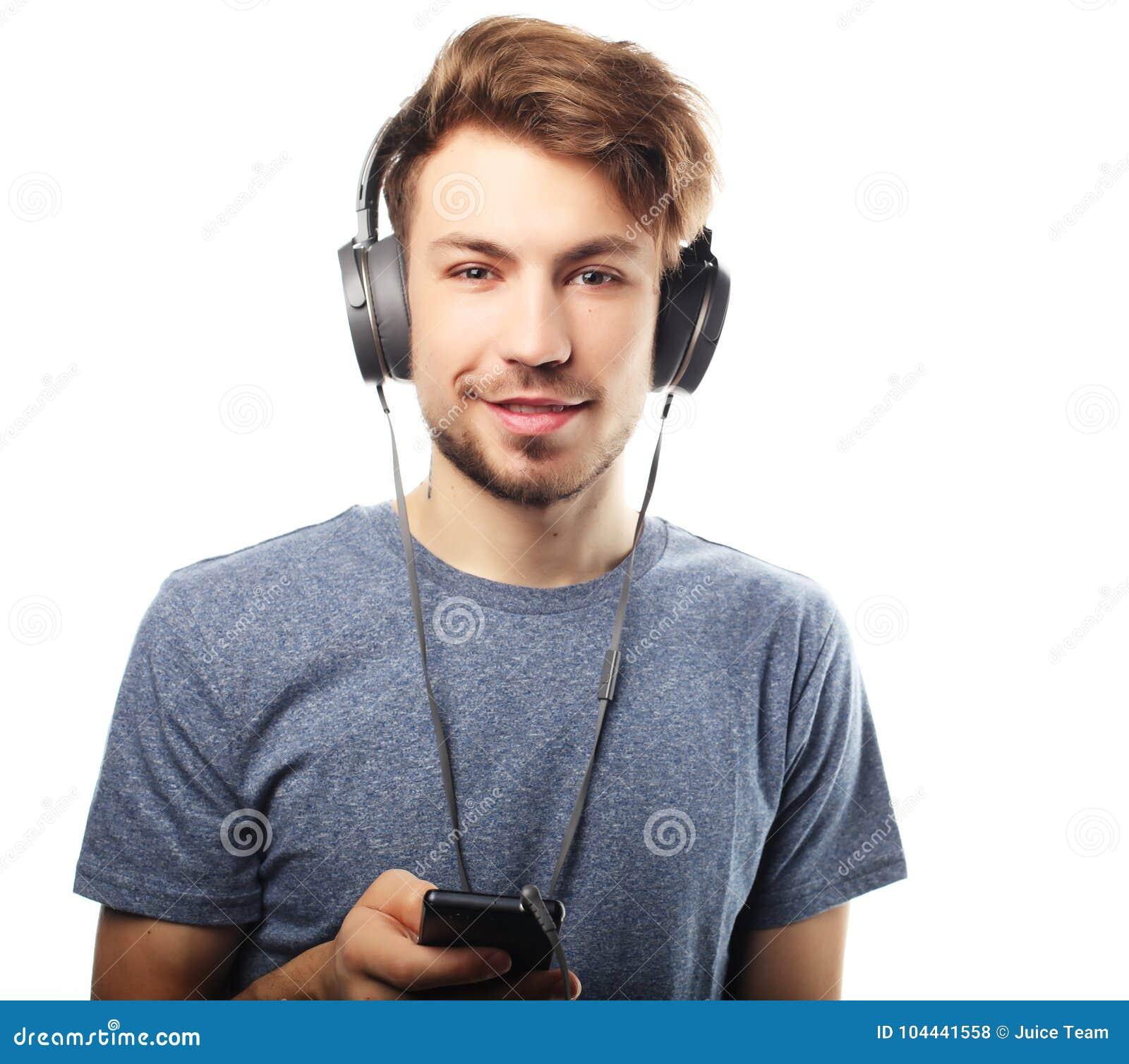 Man den hållande mobiltelefonen och lictening till musik över vit backg
