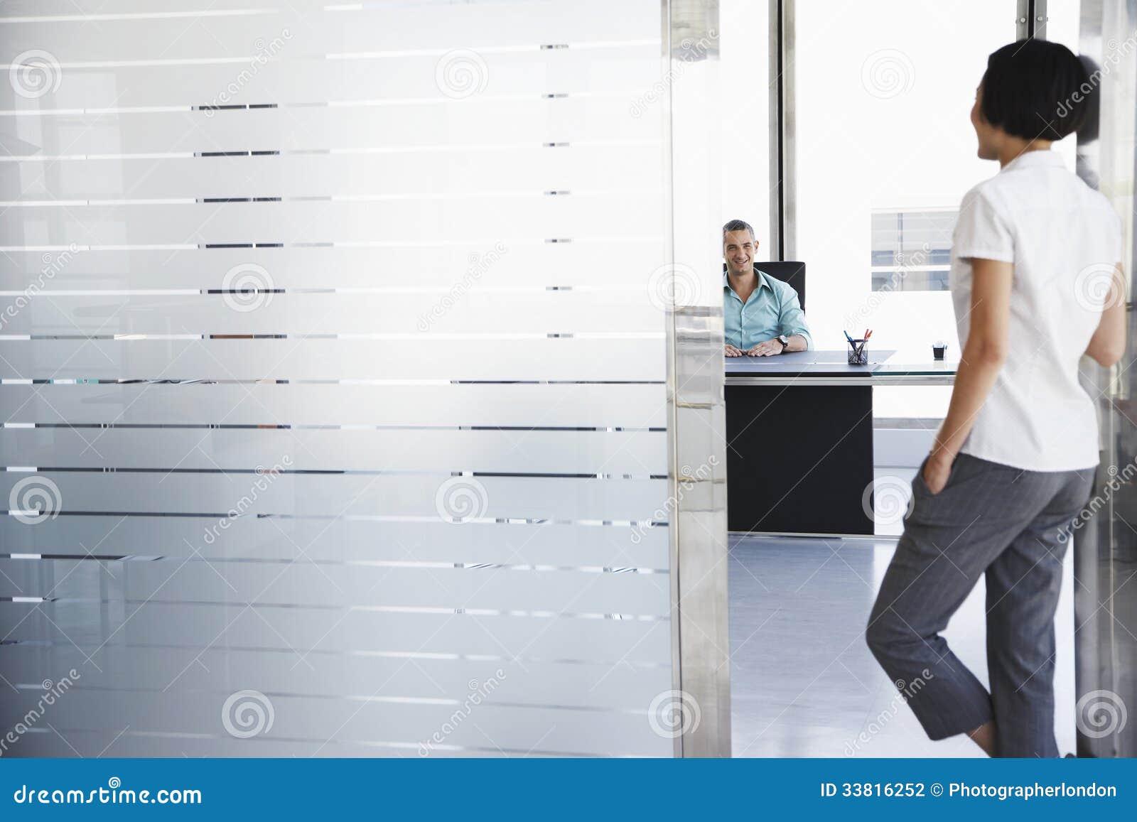 Man die aan Vrouw Status in Bureaudeuropening spreekt