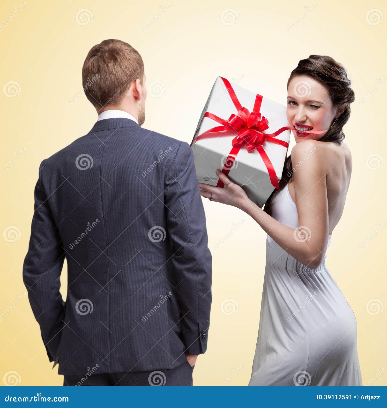 Man die bij het glimlachen van de gift van de vrouwenholding kijken