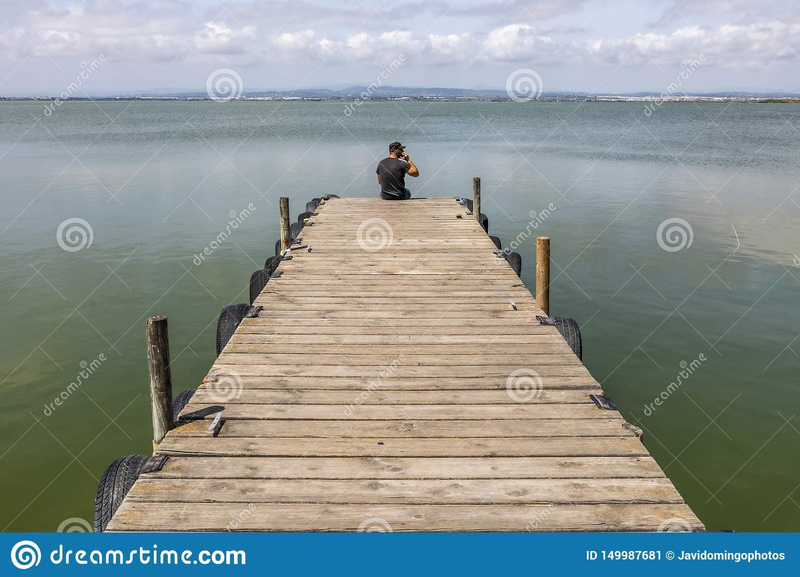 Man On A Dock By The Lake At morning Sky