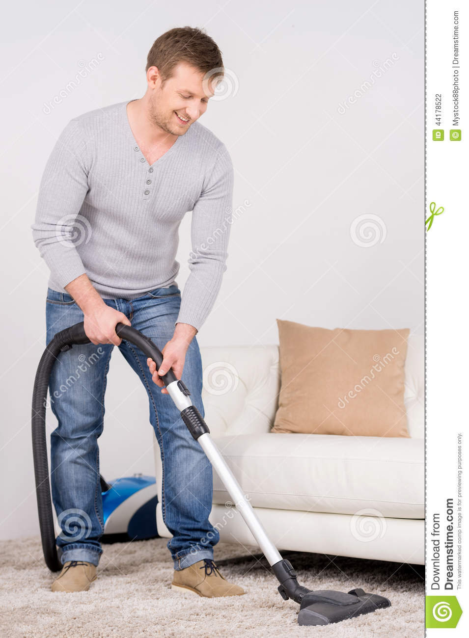 Man Does House Work With Vacuum Cleaner Stock Photo