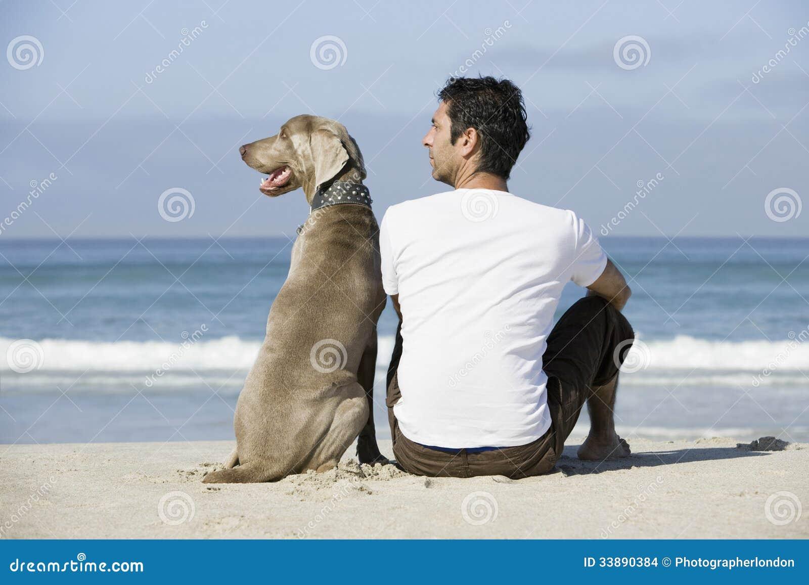 Man And Dog Sitting On Beach