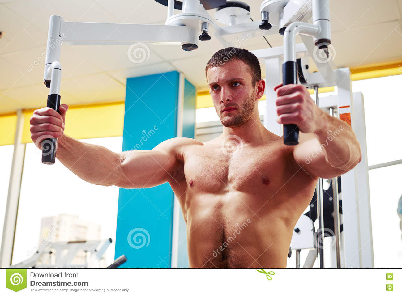 Man Is Doing Chest Workout On The Machine In Gym