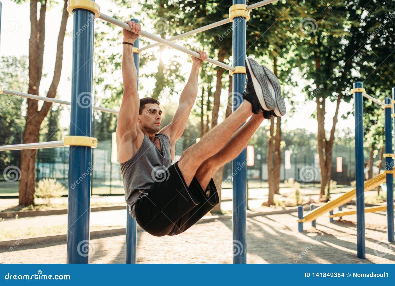 Man doing exercise on press using horizontal bar