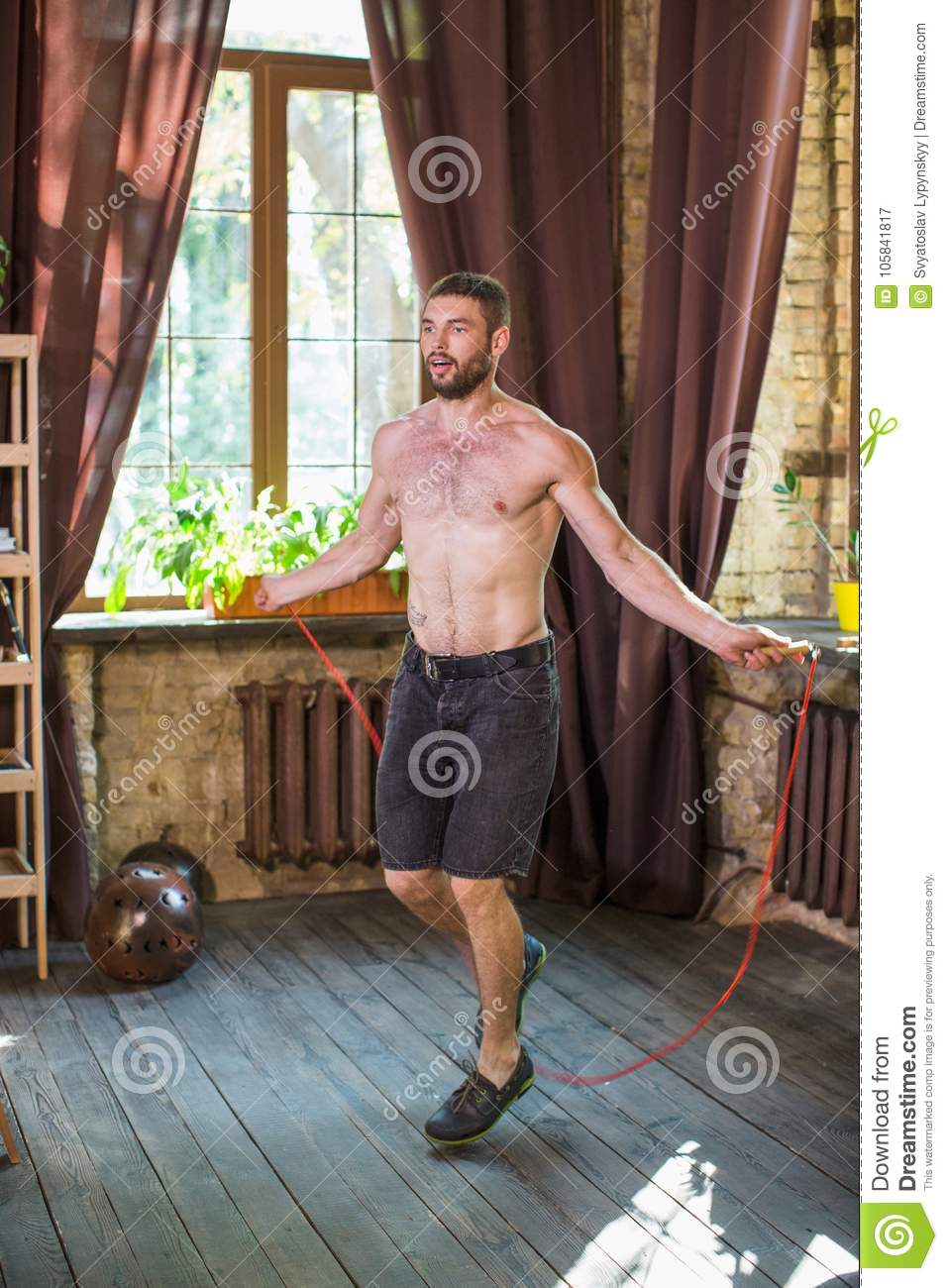 Man Doing Workout Jumping With Rope In Living Room Stock Image