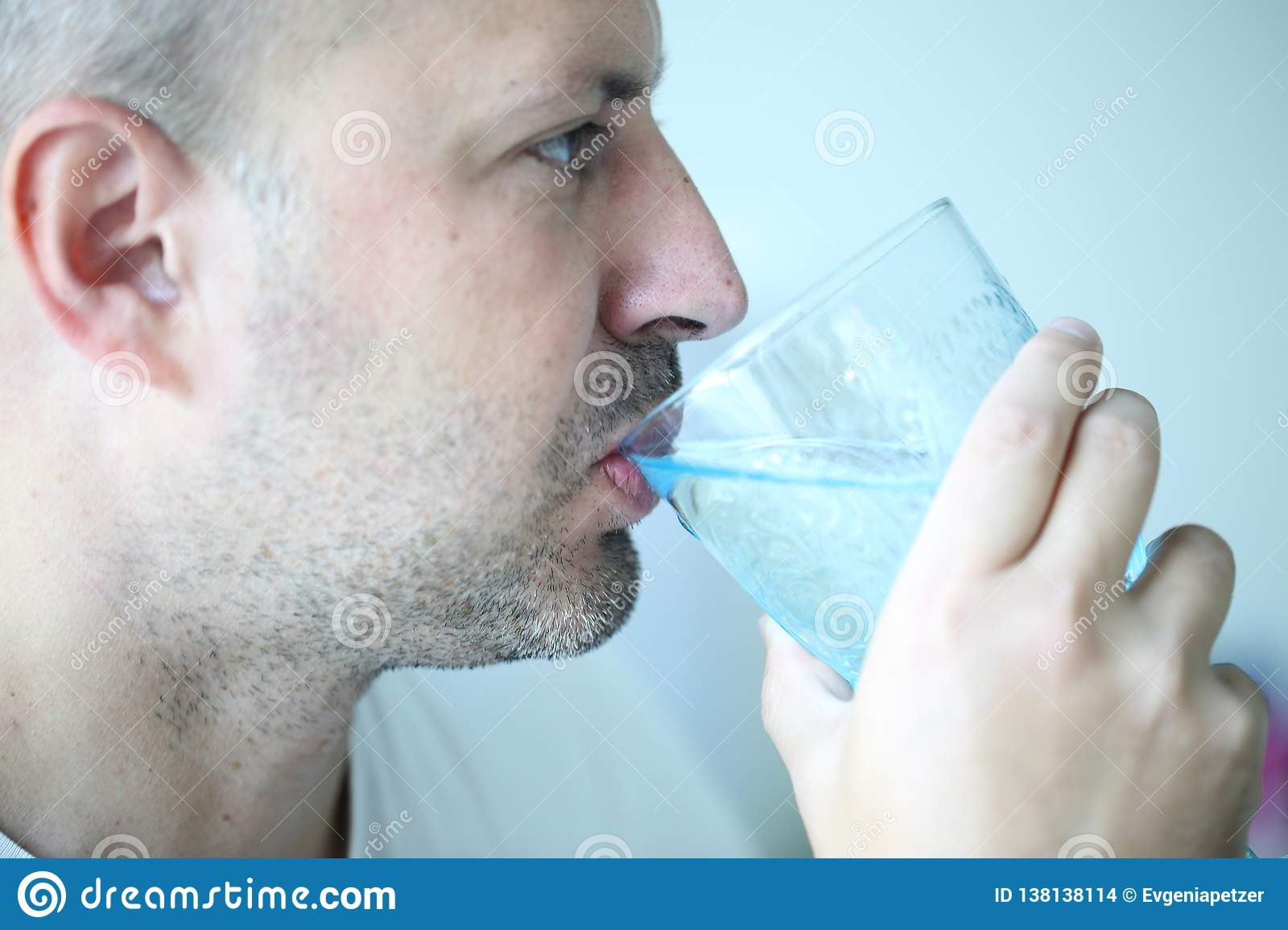 Man is drinking water from a beautiful blue glass