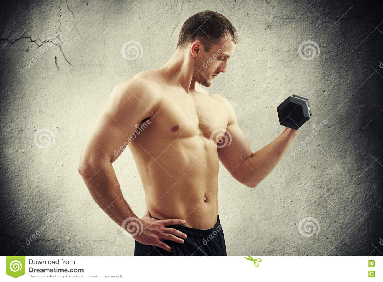 Man with dumbbell flexing biceps over cracked wall