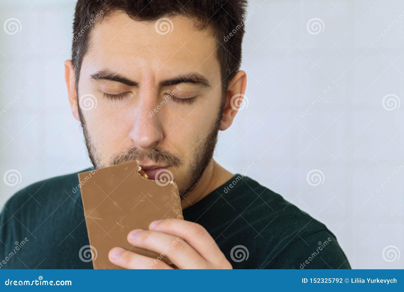 Man eats chocolate with great pleasure