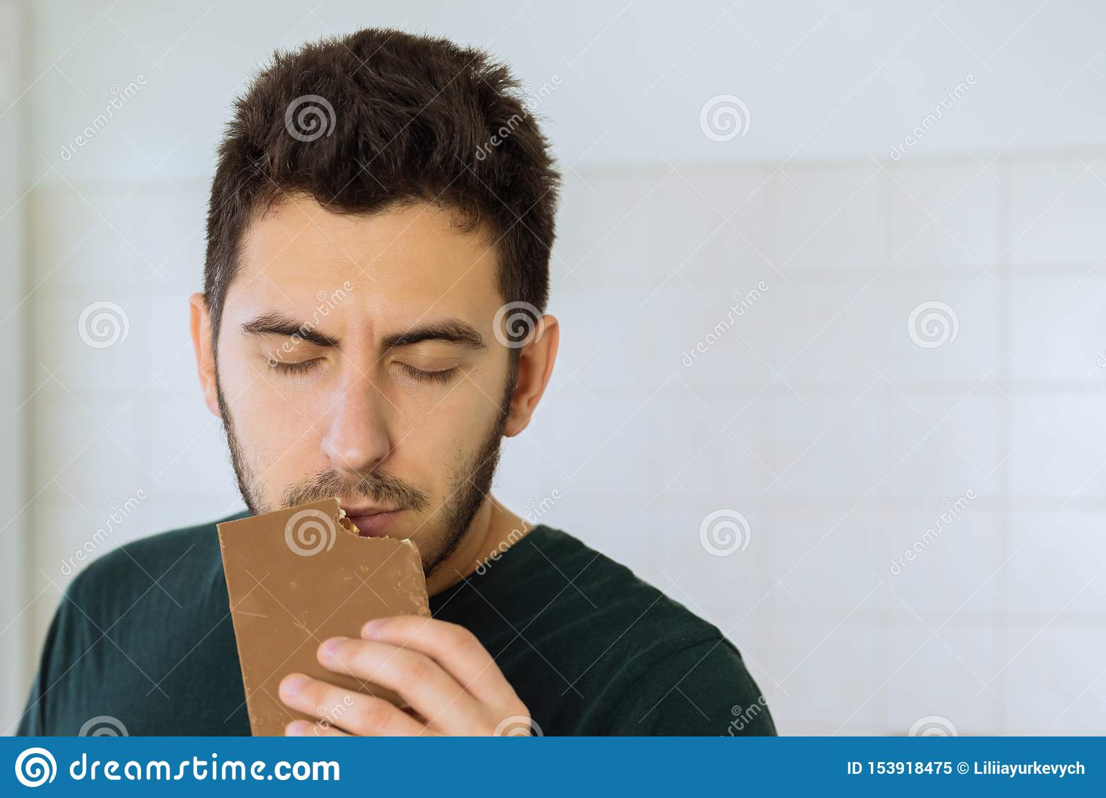 Man eats chocolate with great pleasure. Conceptual photo about sweets.