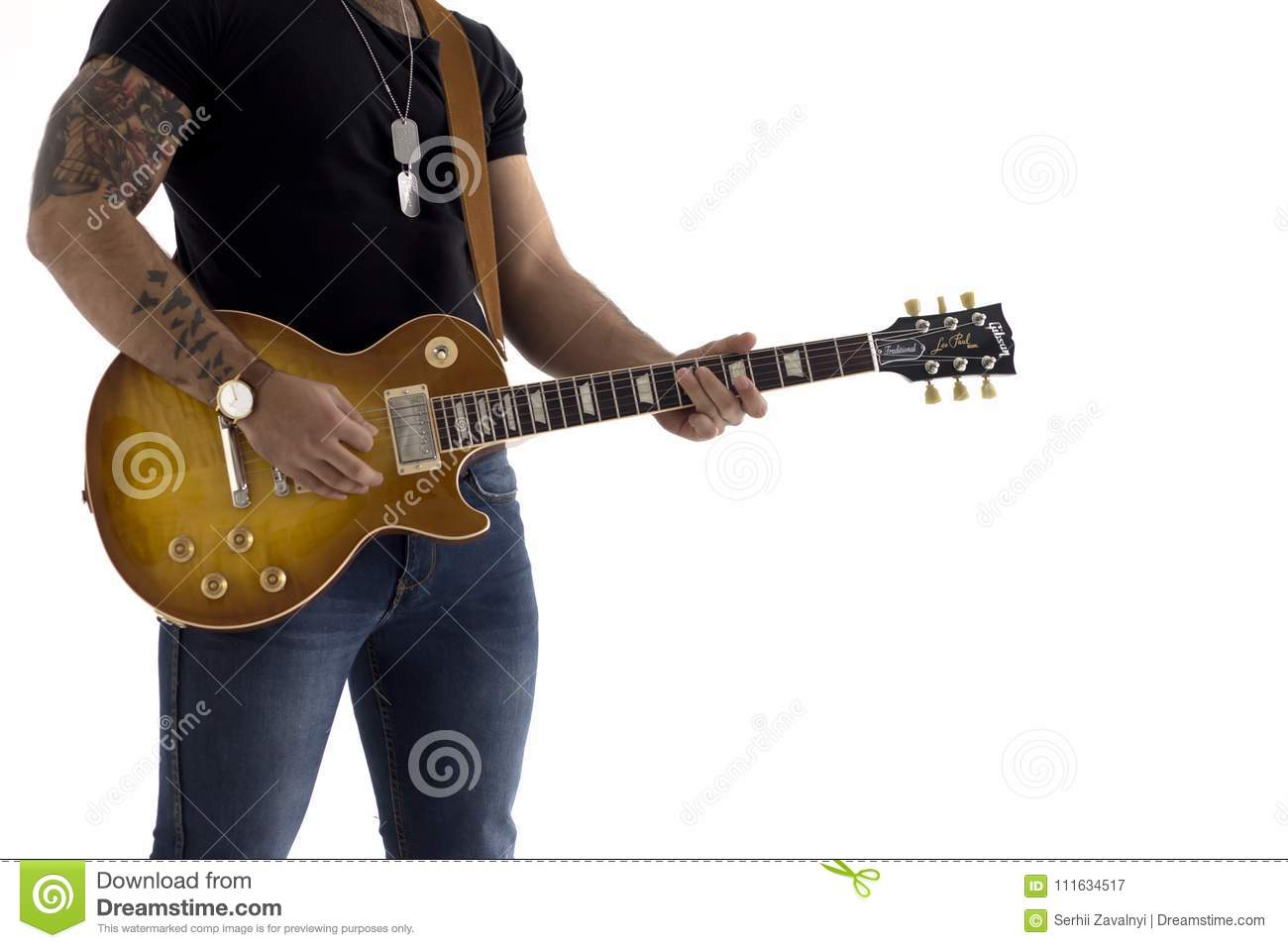 A man with an electric guitar Leaning against a cement wall Happy and relaxed Waiting for the show.