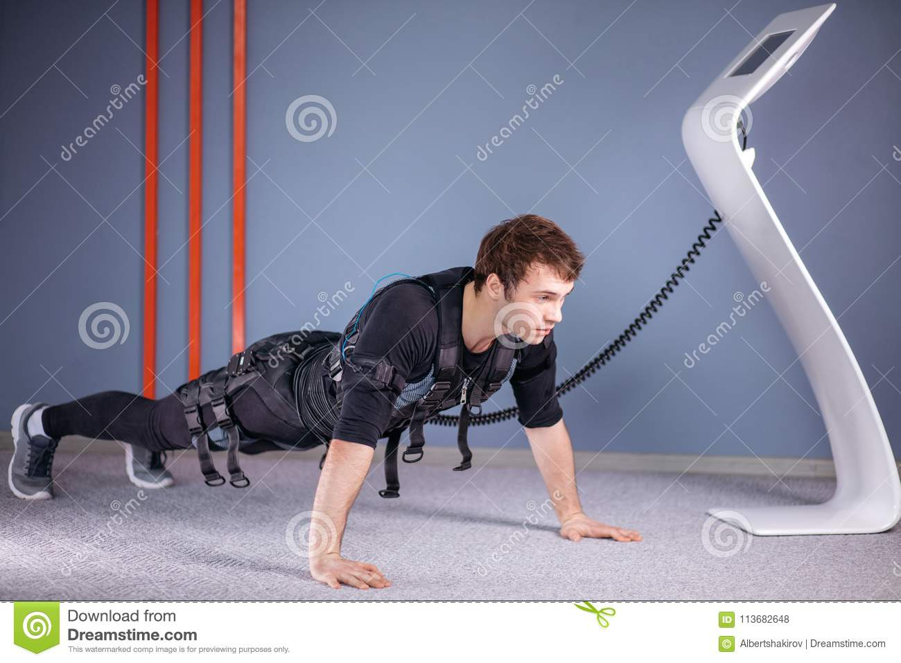 Man in Electrical Muscular Stimulation suits doing plank exercise. EMS