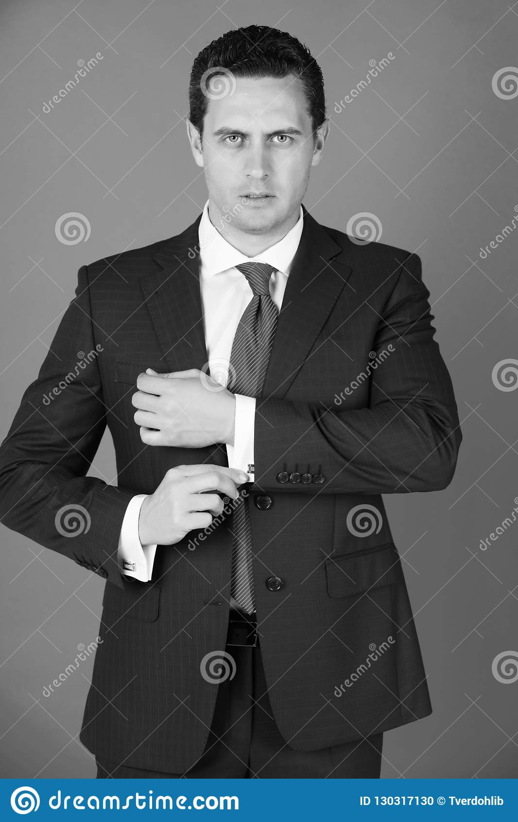 45dbfb6a3 Man, confident businessman or successful boss with stylish hair, haircut in elegant  navy formal suit and tie fixing cufflinks on white shirt on blue ...