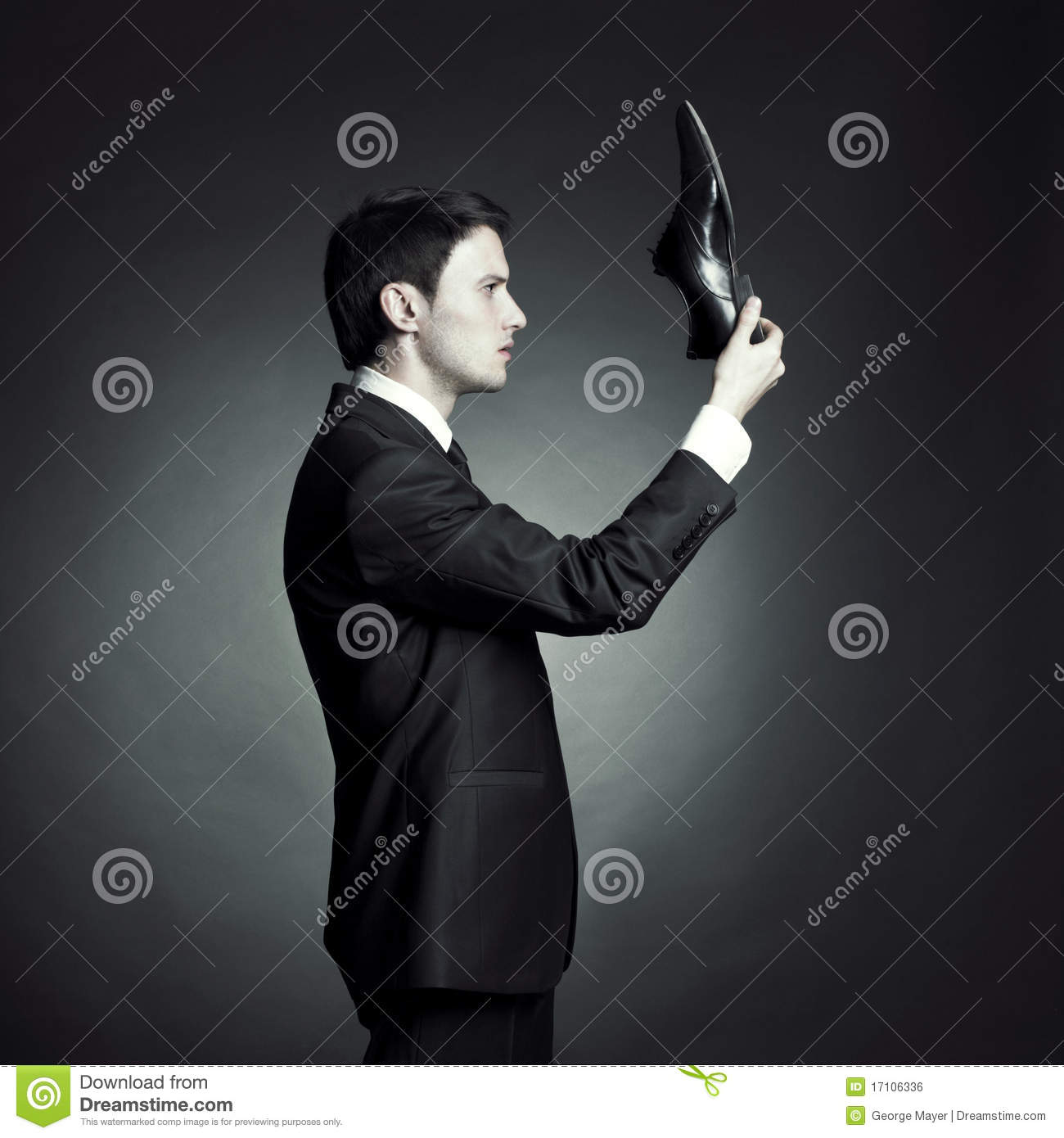 Man in an elegant suit and shoes in hand