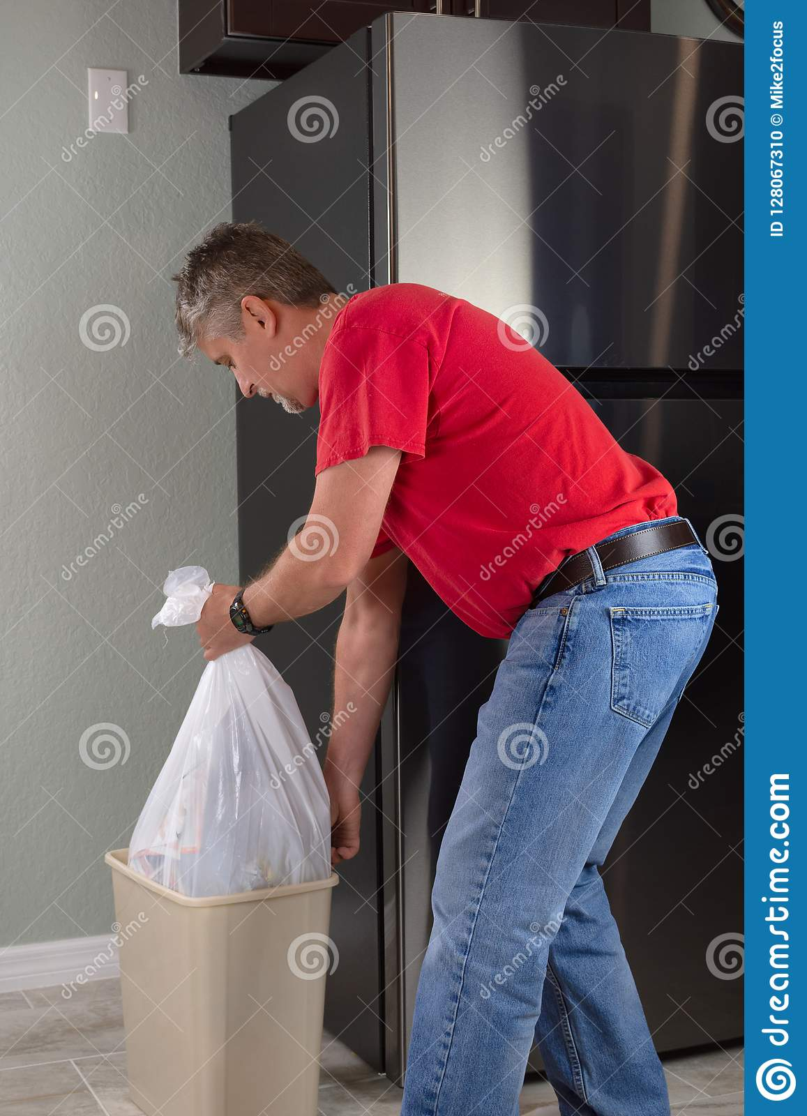 Man emptying trash bag bin container in kitchen to take it out to garbage can