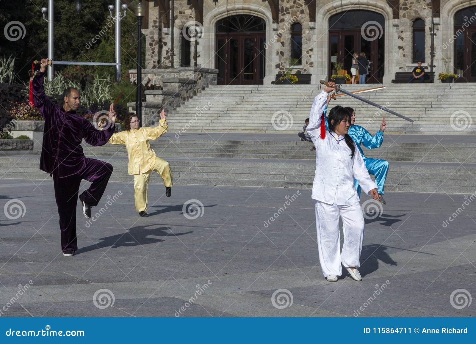 Man en drie vrouwen in Aziatische uitrustingen die aan een Tai Chi-demonstratie deelnemen