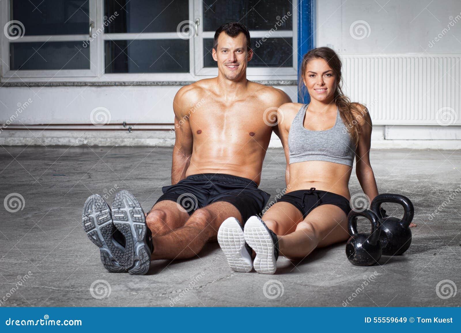 Man en vrouw - de zitting van het geschiktheidsteam op vloer met kettlebells