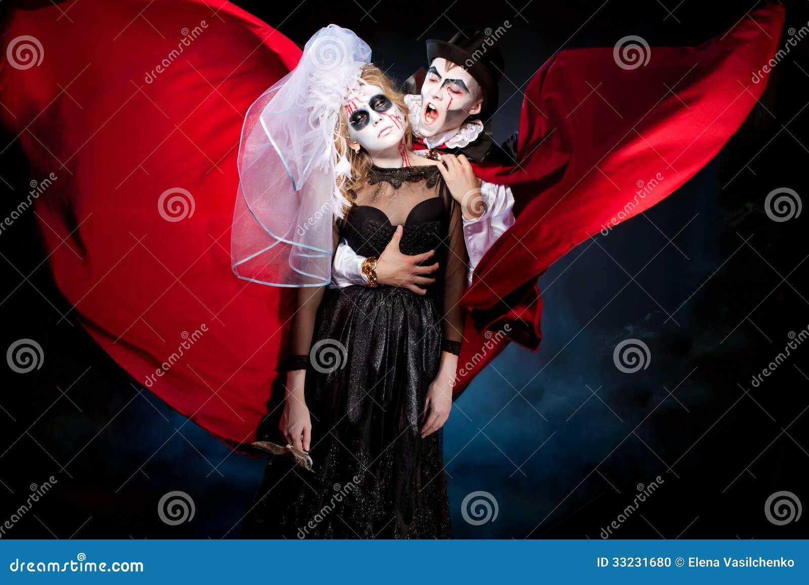 Man en vrouw die als vampier en heks dragen. Halloween