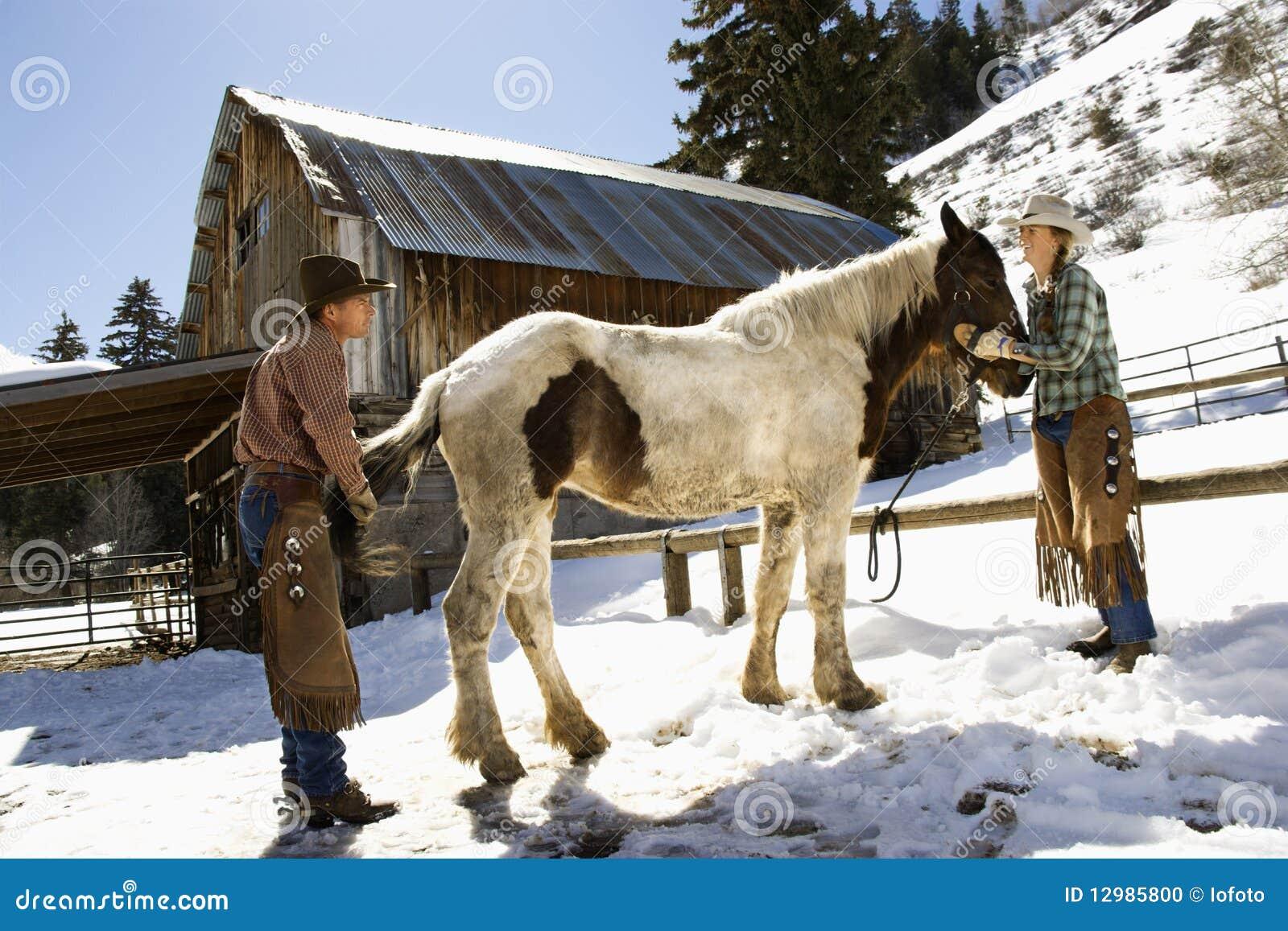 Man en Vrouw die een Paard verzorgen