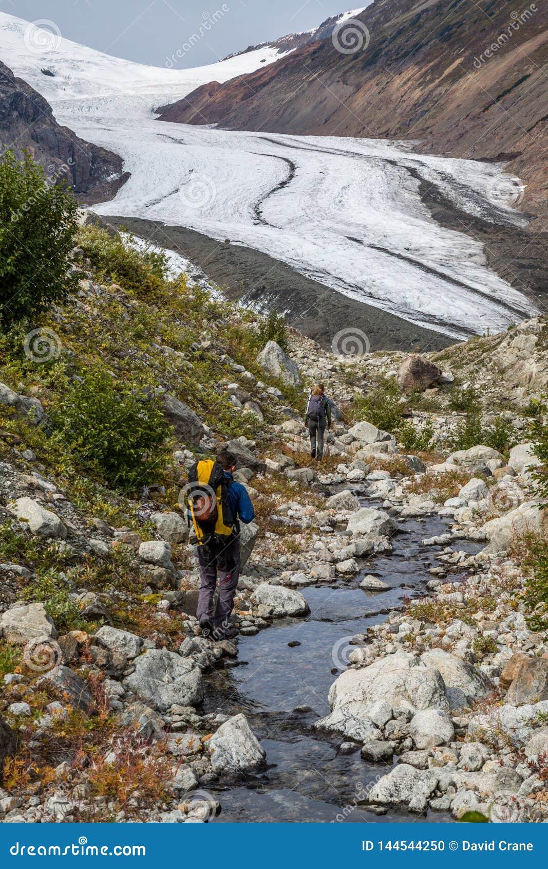Man en vrouw die langs kleine stroom naar Berendon-Gletsjer in Brits Colombia lopen