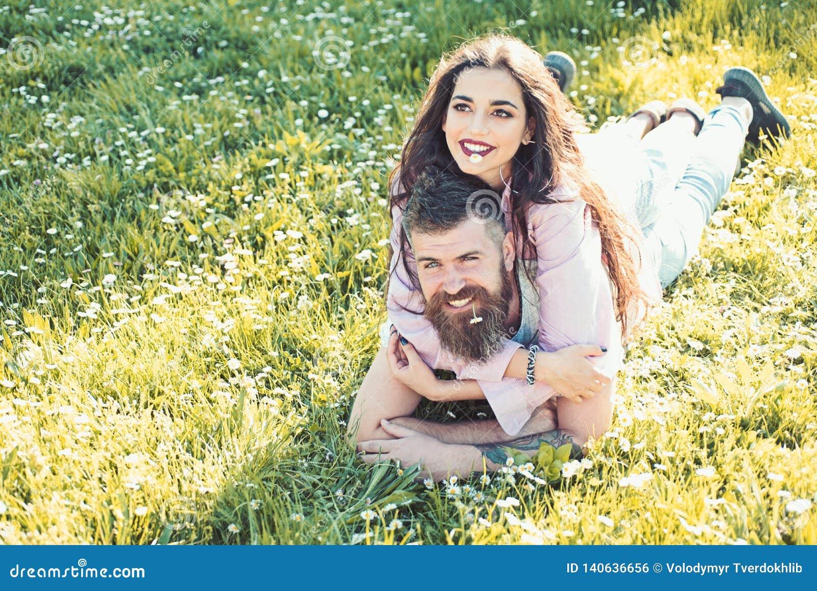 Man en vrouw die op de dag van de graslente leggen het concept van de de lentevrije tijd Paar die op gelukkige gezichten bij weid