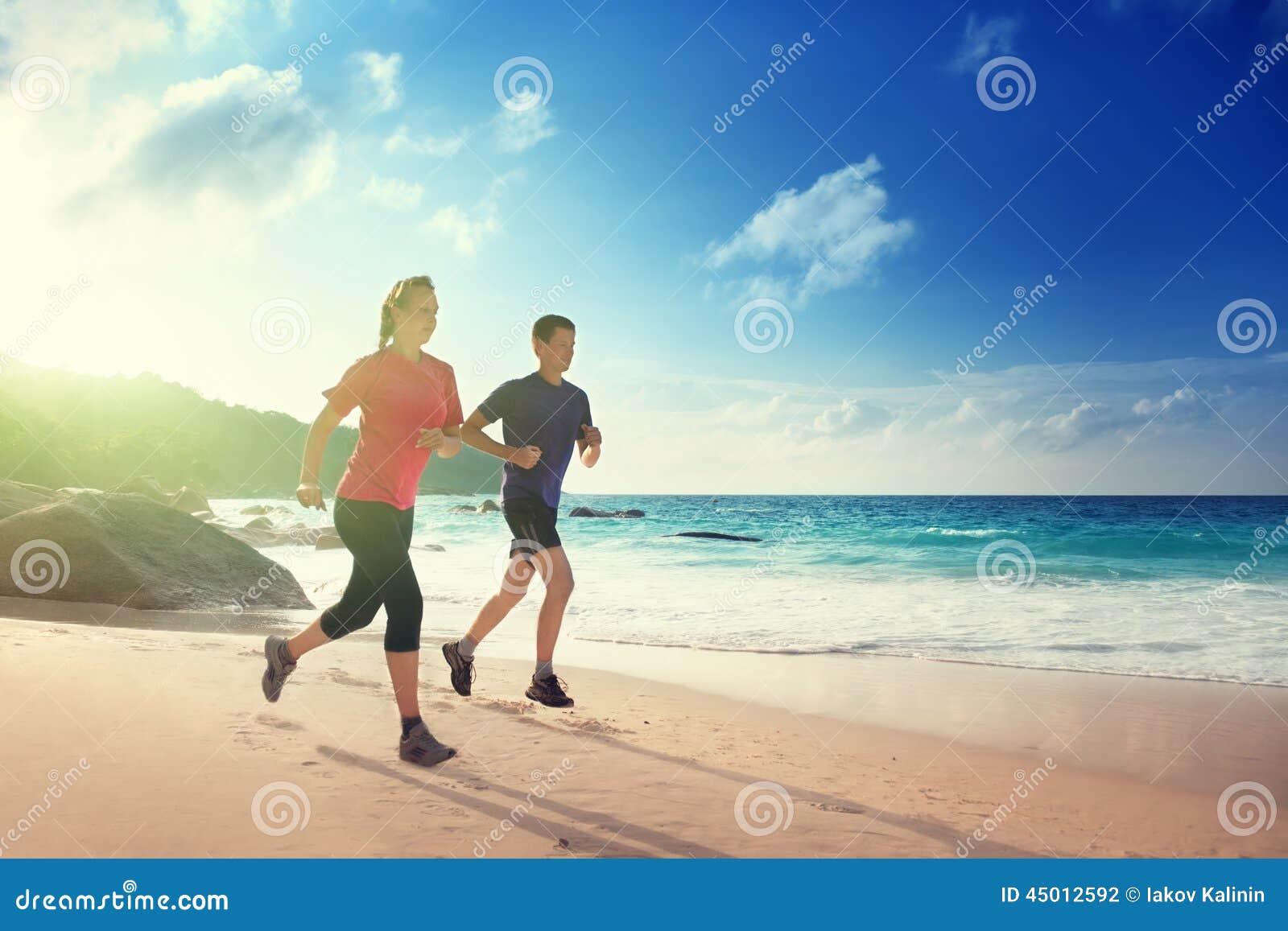 Man en vrouw die op tropisch strand lopen