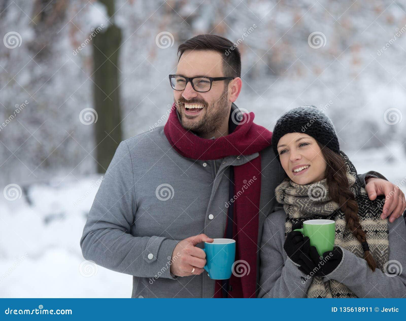 Man en vrouw met hete drank op sneeuw