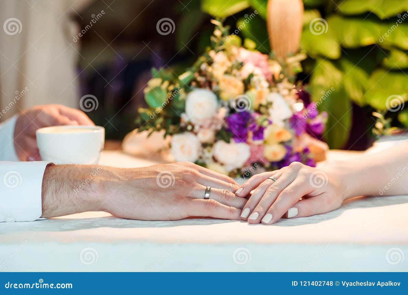 Man en vrouwenhanden met espousal ringen