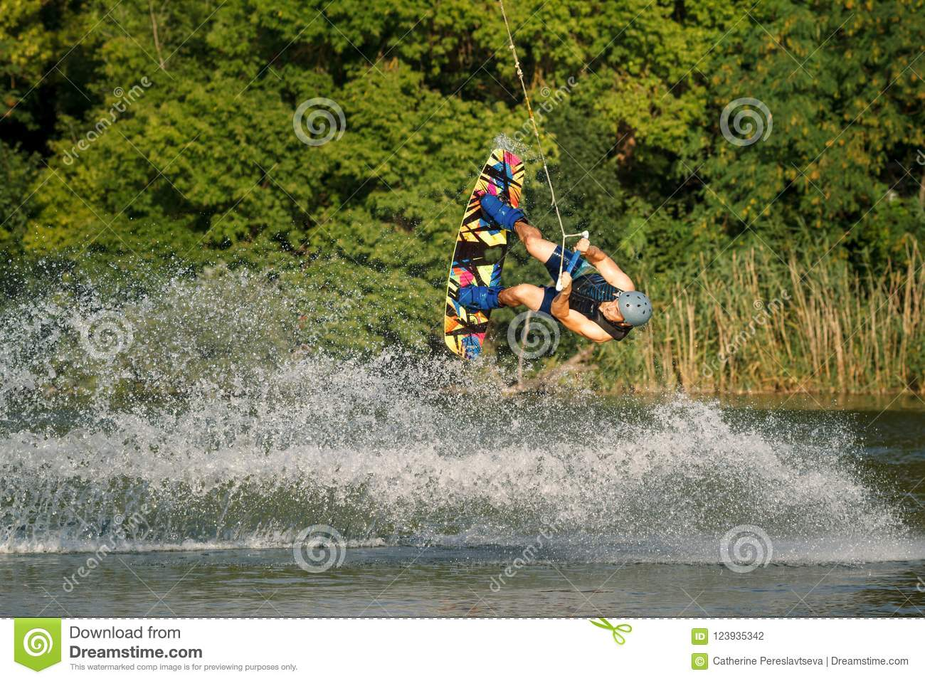 A man engaged in wakeboard on the lake performs jumps