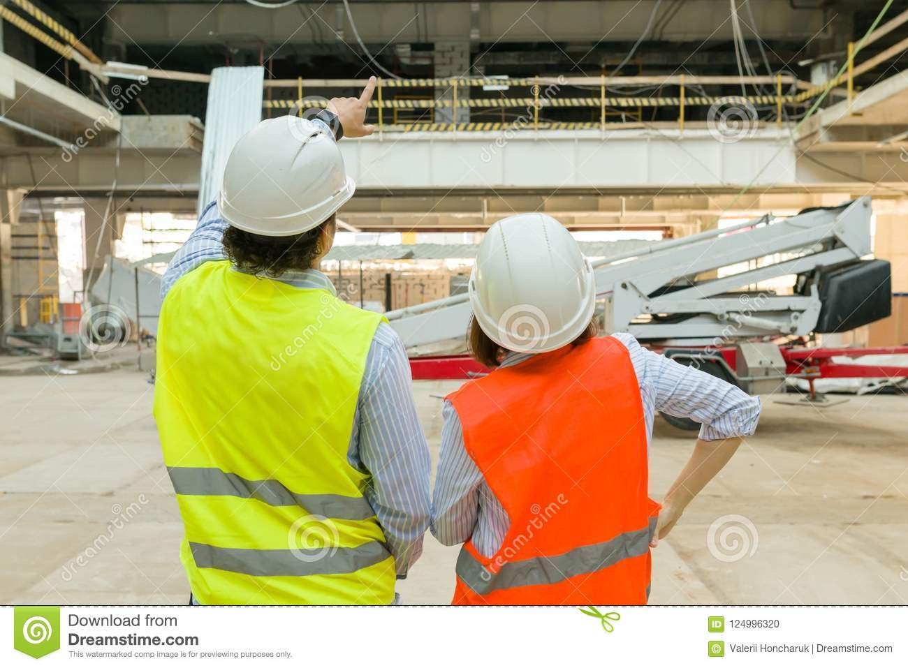 Man engineer and woman architect at a construction site. Building, development, teamwork and people concept