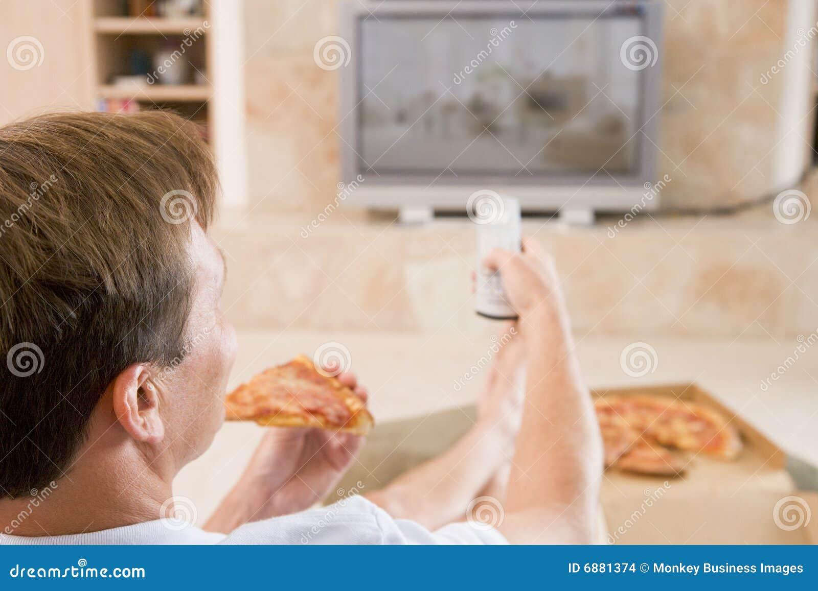 Man Enjoying Pizza While Watching TV