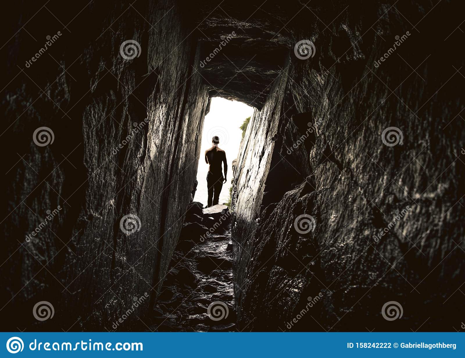 Man in the entrance of a deep narrow cave.