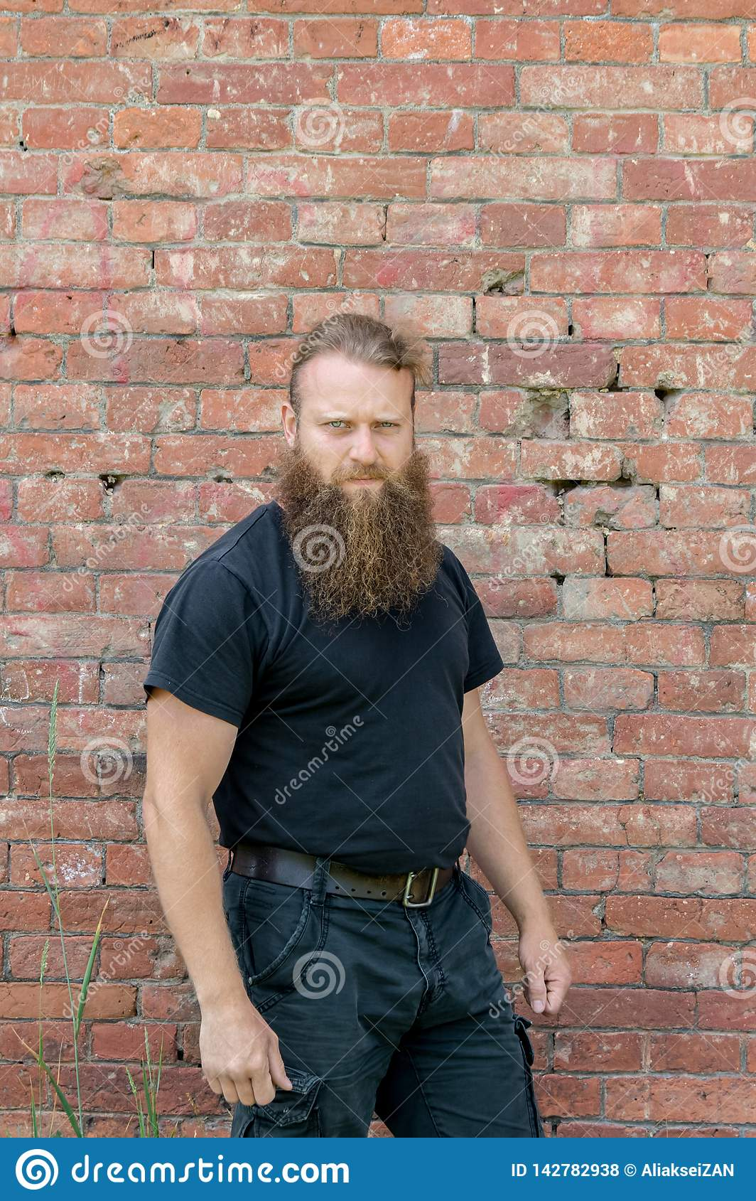 A man, a European with a beard, stands half a turn on the background of a red wall of kerf