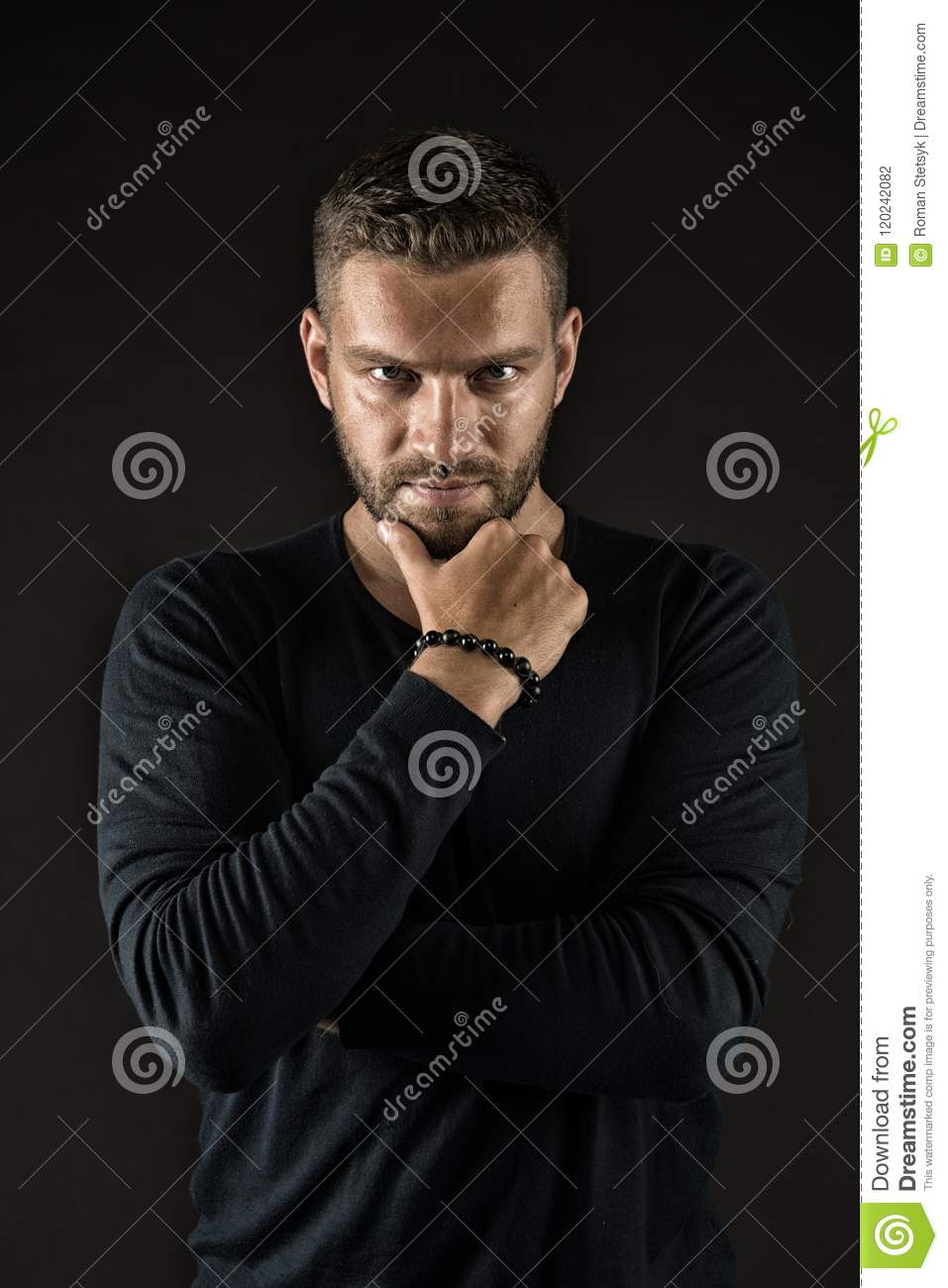 Man with evil look isolated on dark background. Macho touching his beard. Man in black jumper wearing beaded bracelet