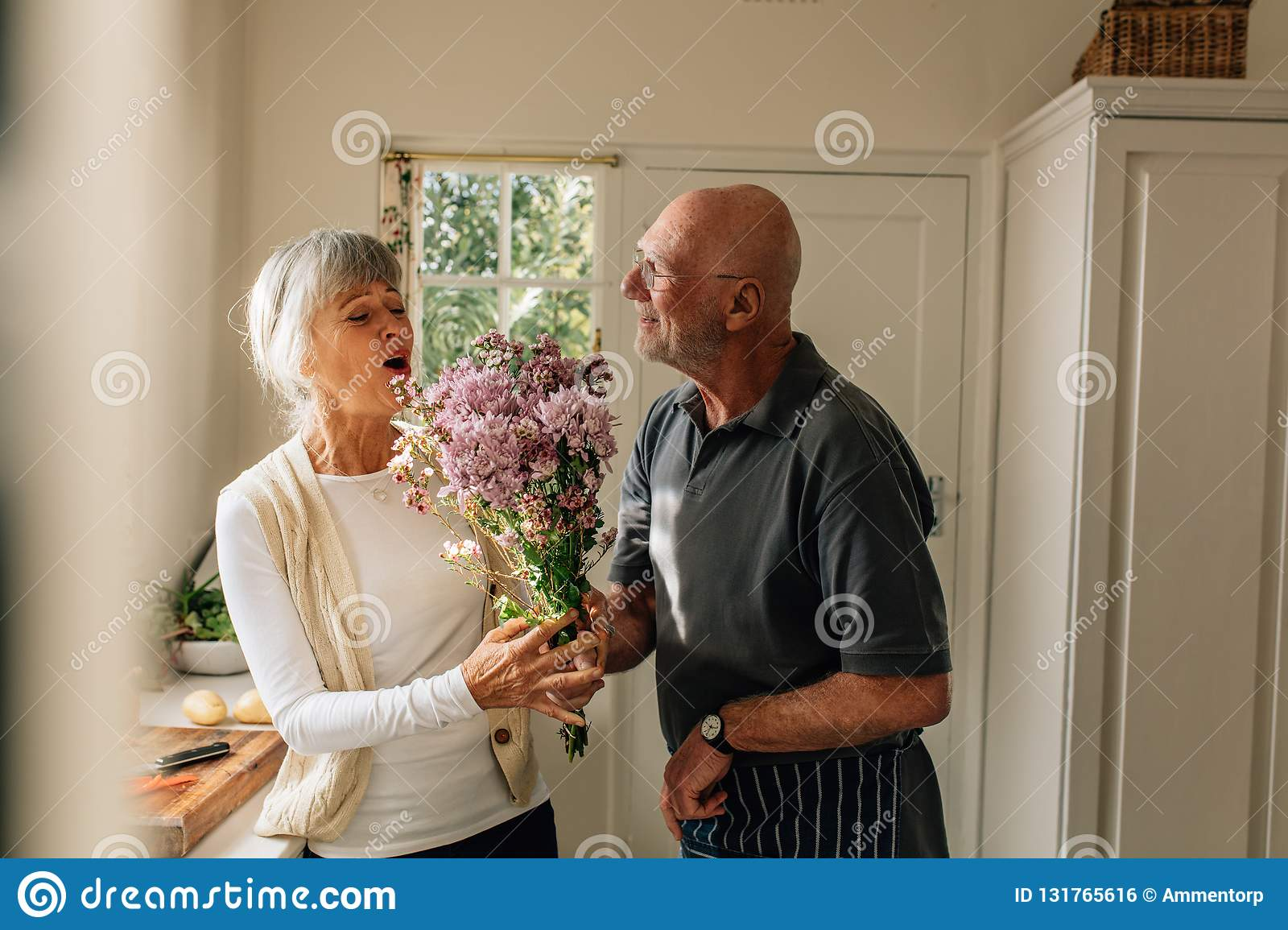 Man expressing his love for his wife giving her a bunch of flowers at home. Senior woman happy to see her husband give her a