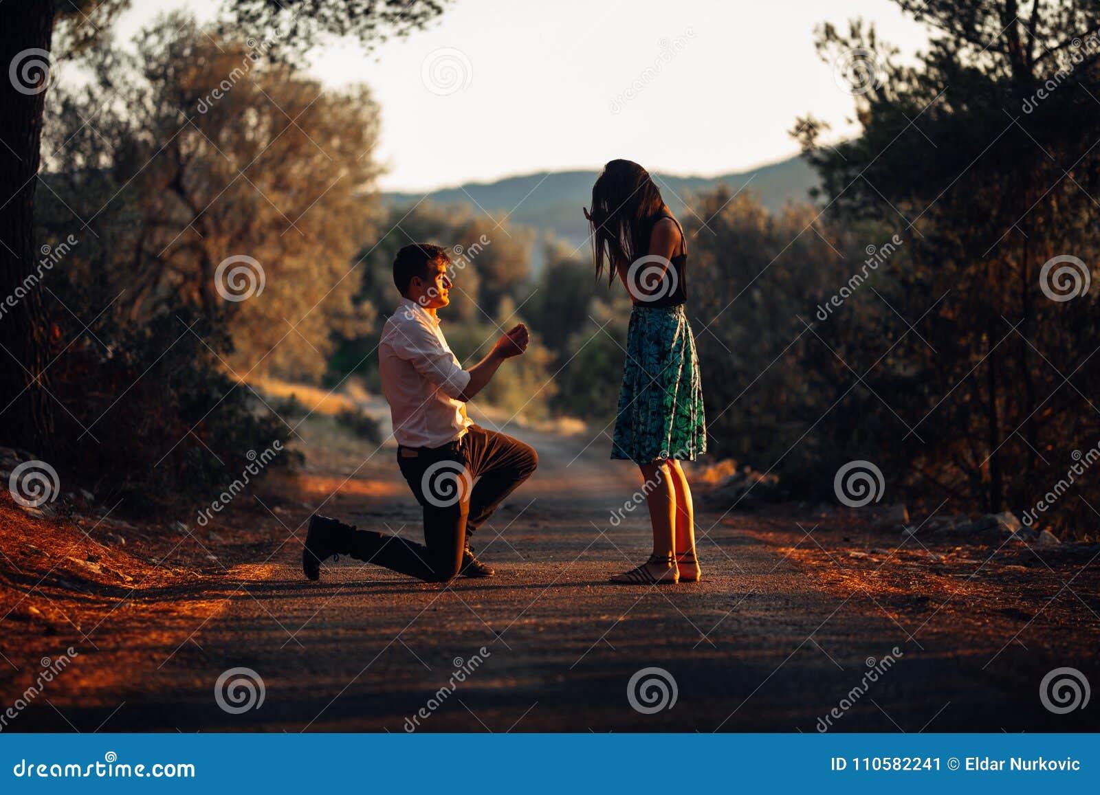 Man förälskat föreslå en förvånad chockad kvinna för att att gifta sig honom på solnedgången Förslag-, kopplings- och bröllopbegr