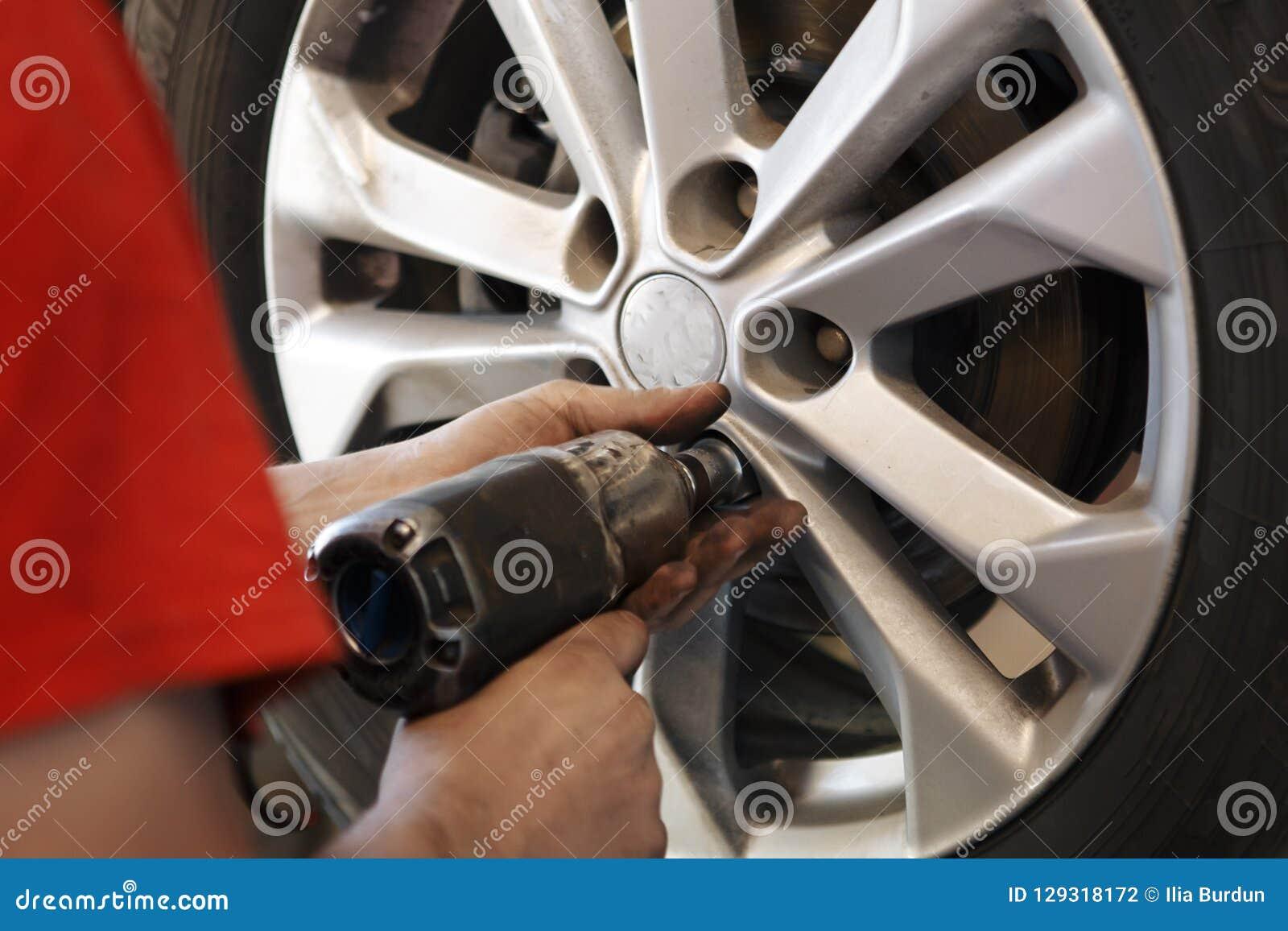 Man för auto mekaniker med det ändrande gummihjulet för elektrisk skruvmejsel utanför service för utbyte för bunkebilelevator lyf