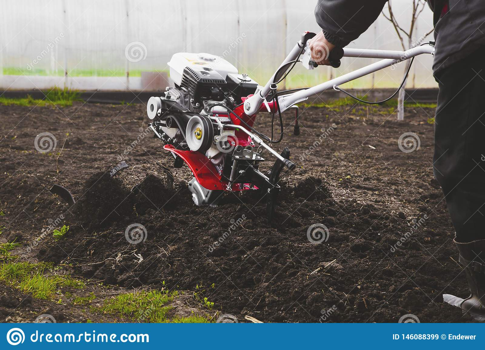 A Man Is A Farmer Plowing The Land In The Garden With A Hand