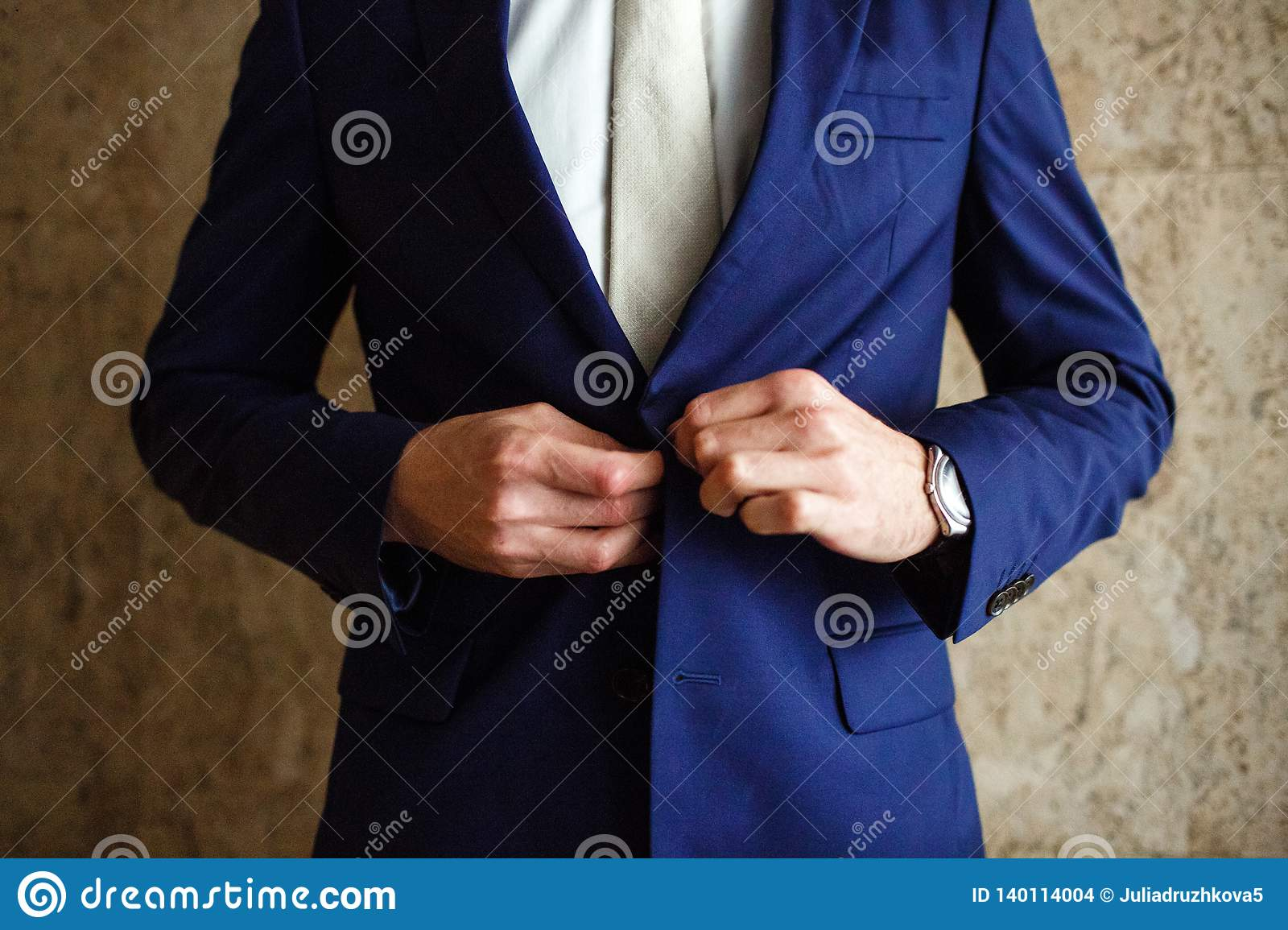 A man fastens buttons blue jacket on his hand his watch