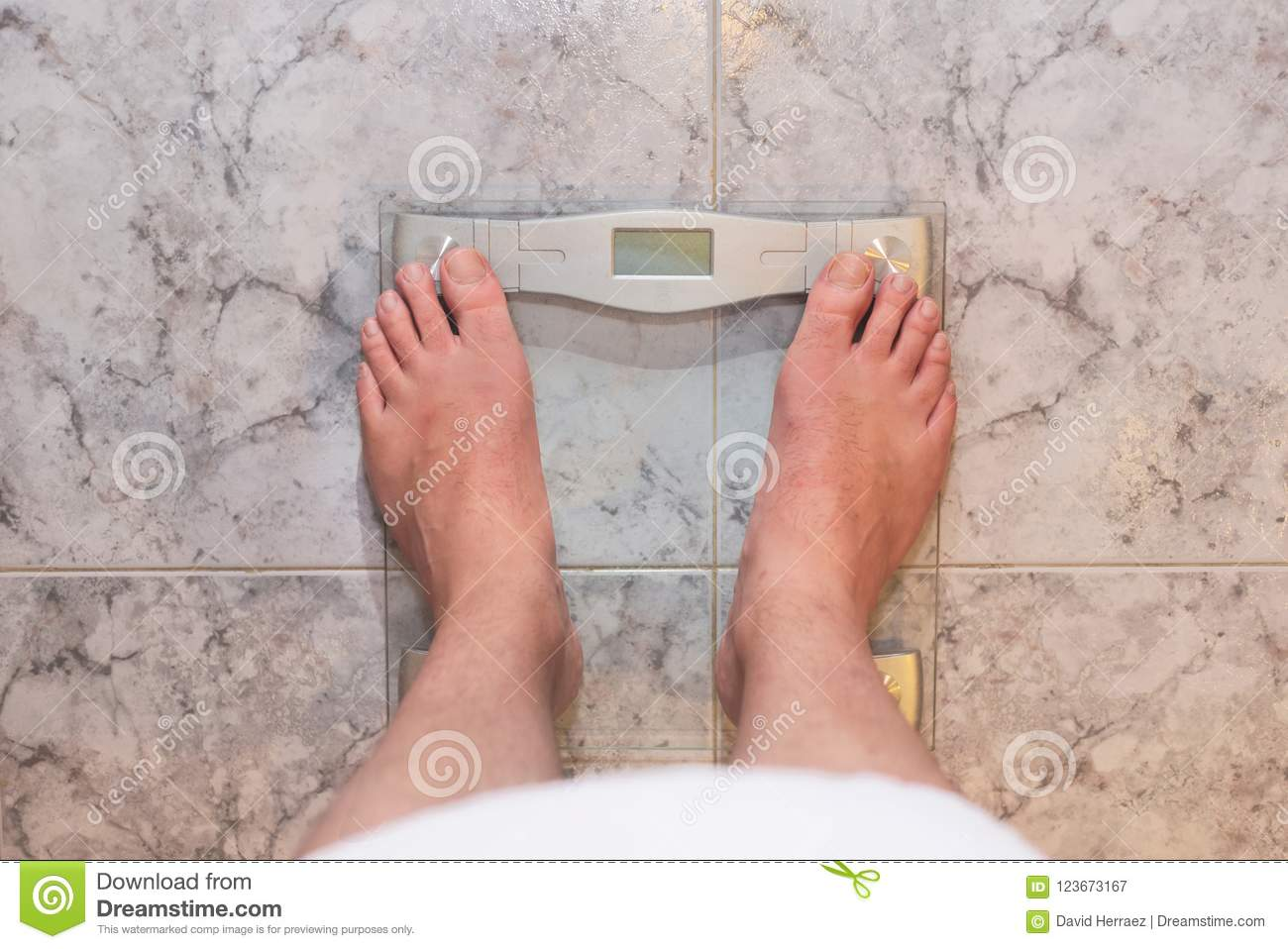 Man feet standing on weight scale