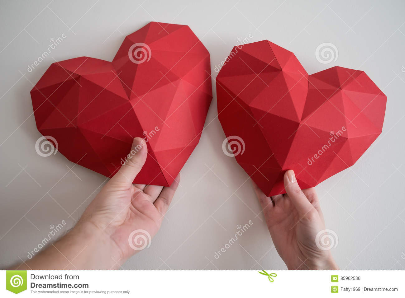 Man and female hands holding red polygonal heart shapes