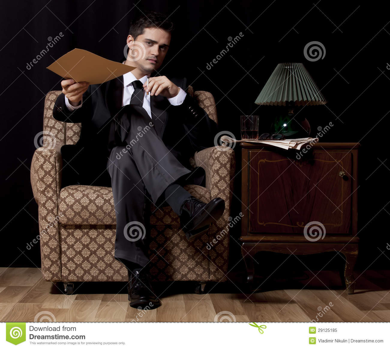 Man with file sitting in vintage armchair royalty free for Sitting in armchair