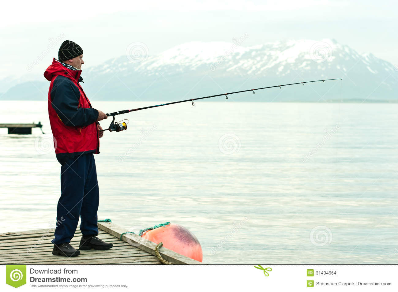 Side view of man fishing in fiord with snow capped mountain in ...