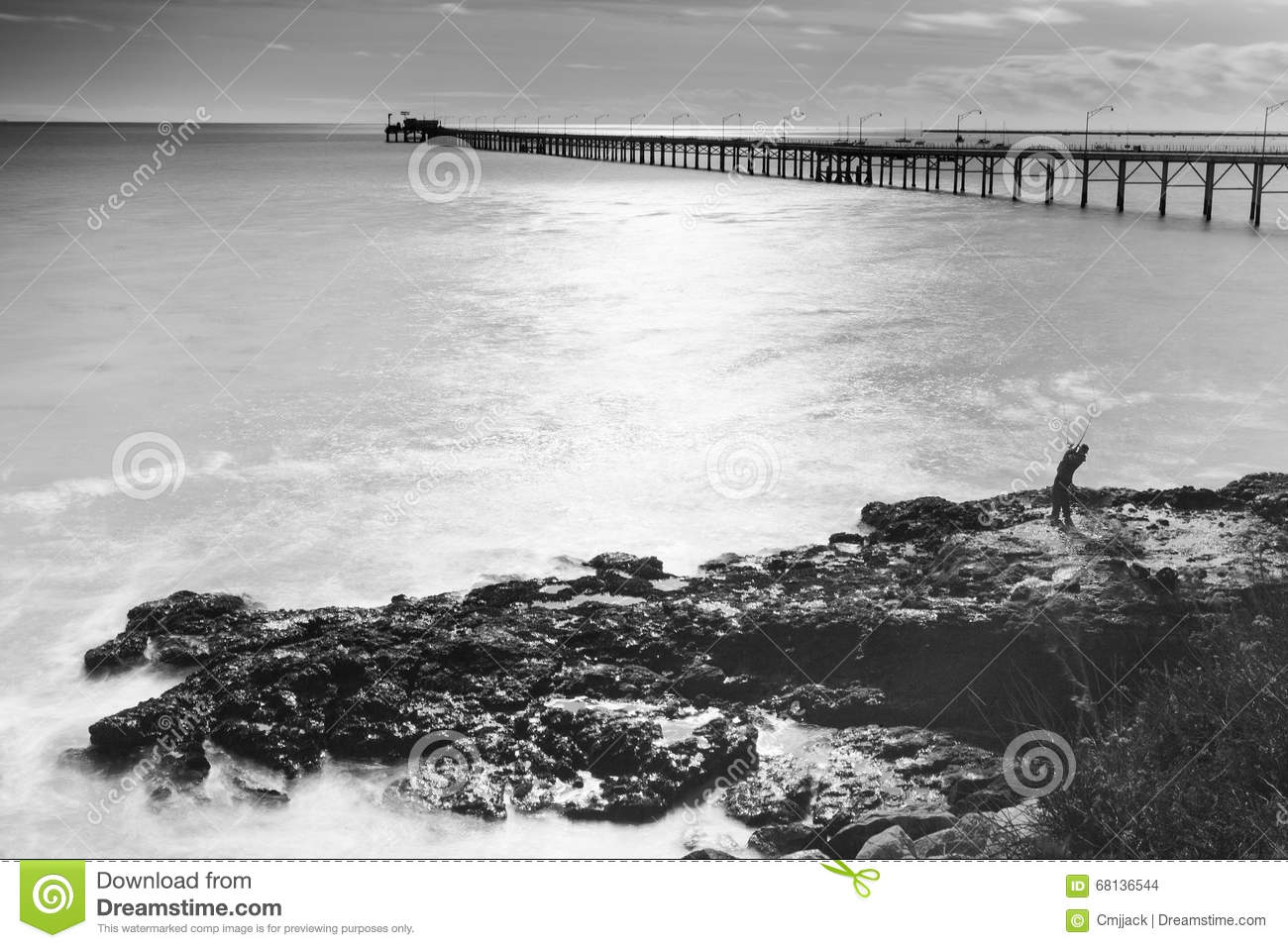 a man fishing on a rock facing the pacific ocean with a view of a