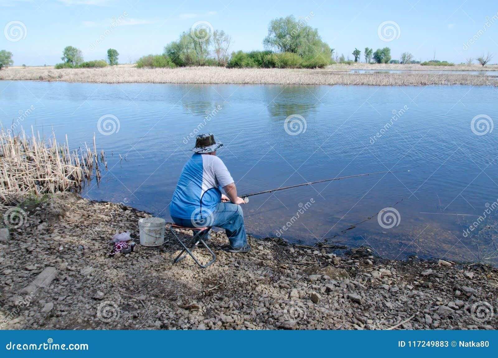 Man fiskesammanträde på en stol på flodbanken