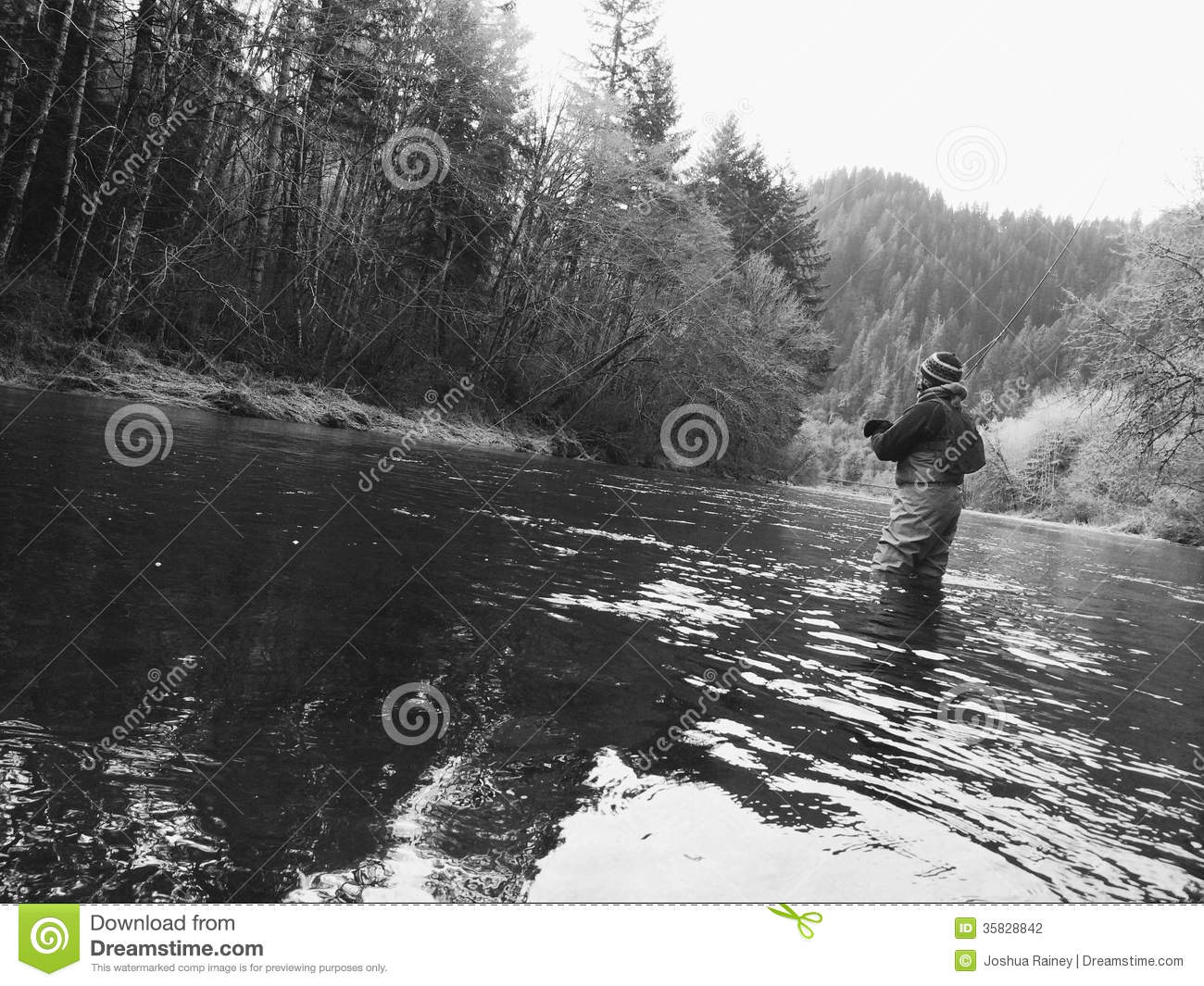 Man fly fishing in cold winter weather stock photo image for Fishing in cold weather